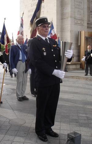 Le lieutenant des sapeurs-pompiers Pierre Villette tenant la Flamme sous l'Arc de Triomphe.